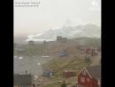 Приближение огромного айсберга к маленькой деревни Innaarsuit в Гренландии
