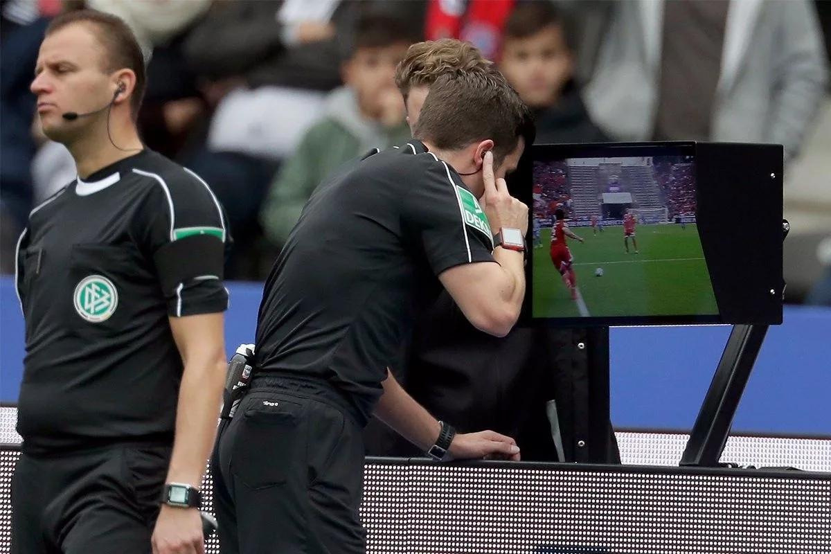 Арбитр просматривает эпизод с помощью системы ВАР. Футбол